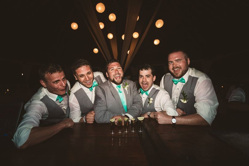 Groomsmen laugh with tequila