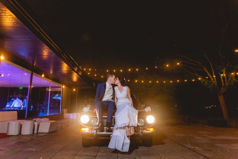 Newlyweds sit on a car & kiss