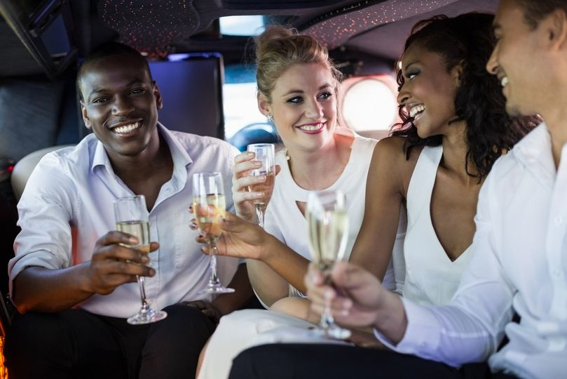 well dressed people drinking champagne in a limousine on a night out 51 1056011 v1
