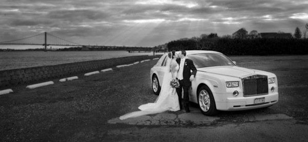 Newlyweds by their wedding car