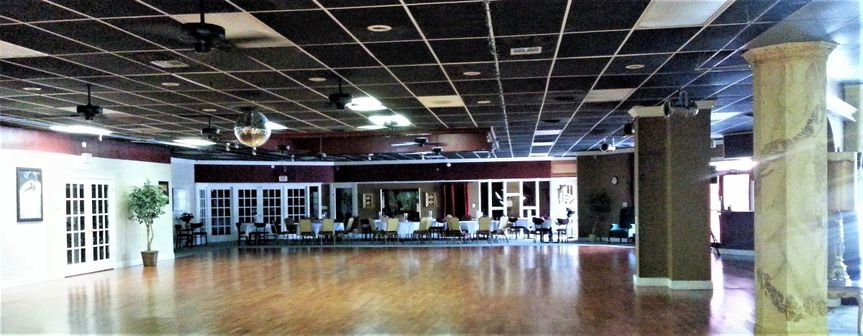 Dance floor with carpeted seating area and DJ booth.  Glass French doors lead to two junior...