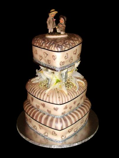 The layers of this old-fashioned wedding cake are heart shaped hat boxes. Done in modest, rustic...
