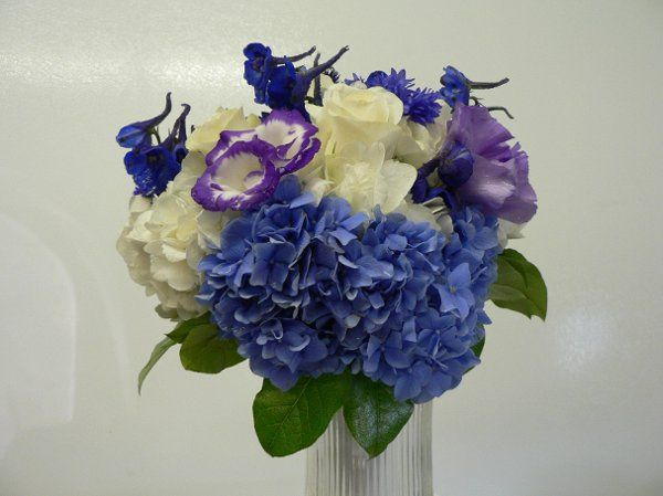 Handtied bouquet of blue and white hydrangias, purple two-tone lizzianthus and delphinium
