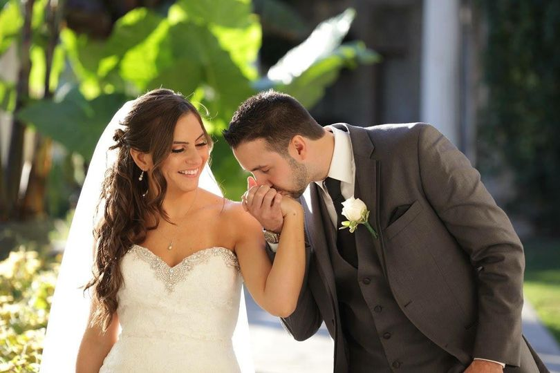 Groom kissing bride on hand