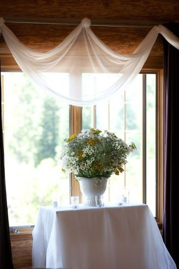 The wedding centerpiece of Shasta daisies, monte casino, and yellow mums, with Queen Ann's lace,...