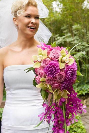 A cascading bouquet of roses, dahlias, green cymbidium orchids, lily grass, and mokara orchids....