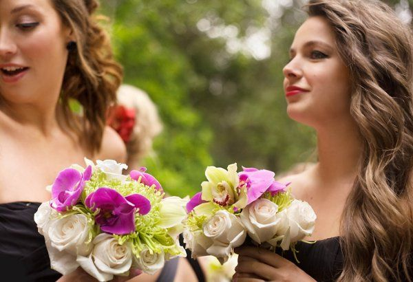 The bridemaids' bouquets consists of ivory roses, large green spider mums, and phalaenopsis orchids.