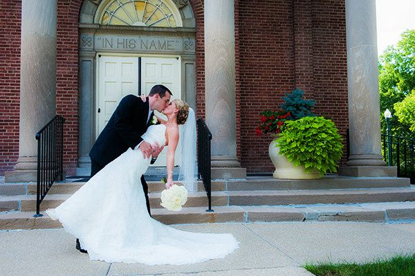 groom dipping bride in front of churc