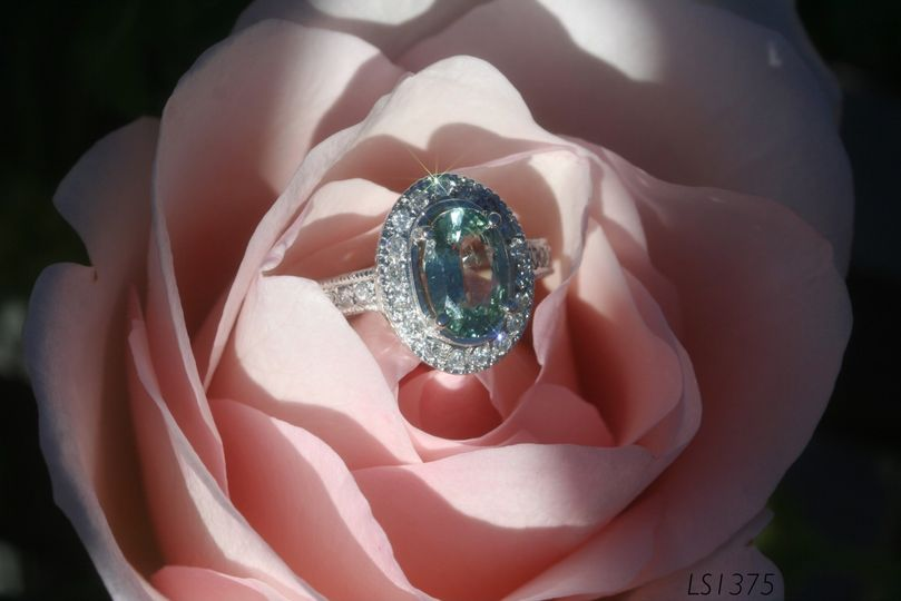 Enjoy this stunning oval green sapphire engagement ring with a pave diamond halo!  See full details...