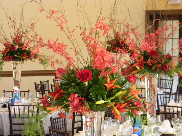 Tall centerpieces with orchids, lilies, roses and greens