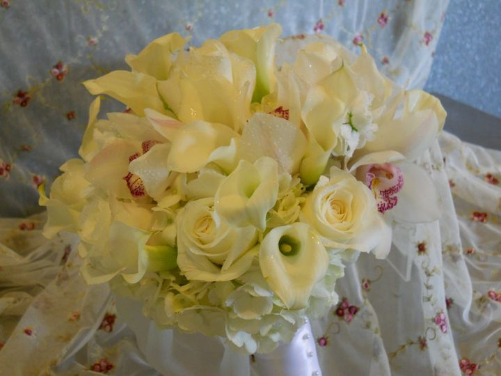 Bridal bouquet with roses, mini calla lilies, hydrangea, cymbidium orchids, lisianthus and white...