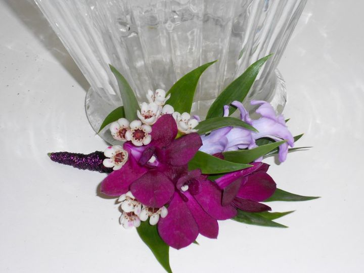 Boutonniere with dark purple dendrobium, hyacinth blooms and waxflower