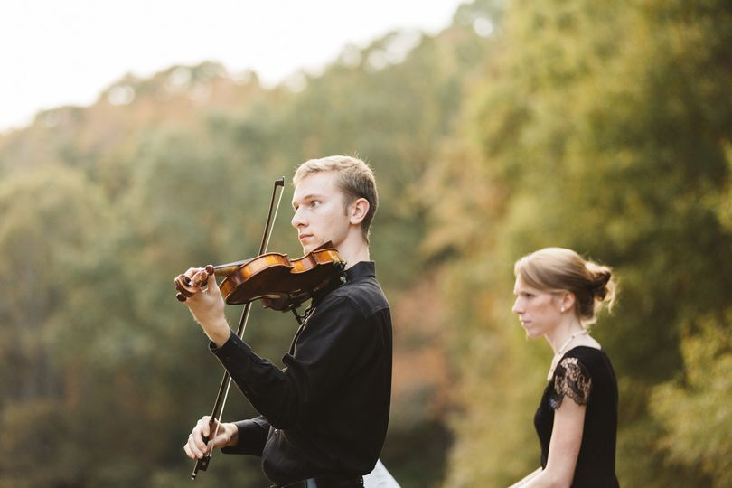 Violinist performing in a forest