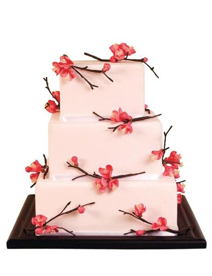 Square cake covered in piank fondant and decorated with red gumpaste quince blossoms