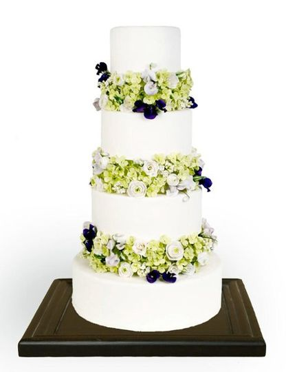 Cake covered in white fondant with tiers separated by sections of gumpaste hydrangeas, lisianthus,...