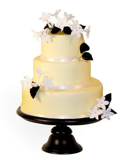 Round cake covered in yellow fondant with oversized gumpaste stephanotis blossoms created for The...