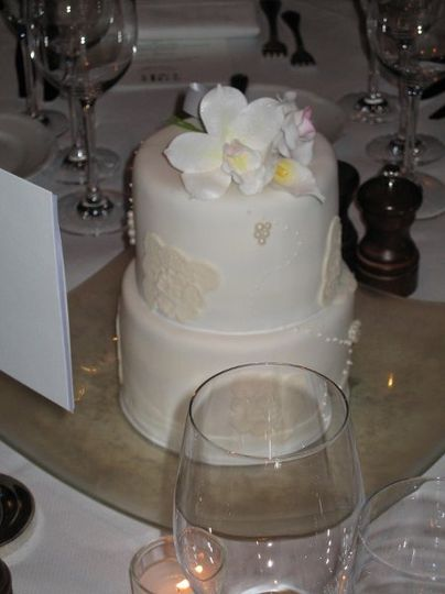 Tabletop cakes decorated with handmade gumpaste orchids, calla lilies, sugar lace, and edible...