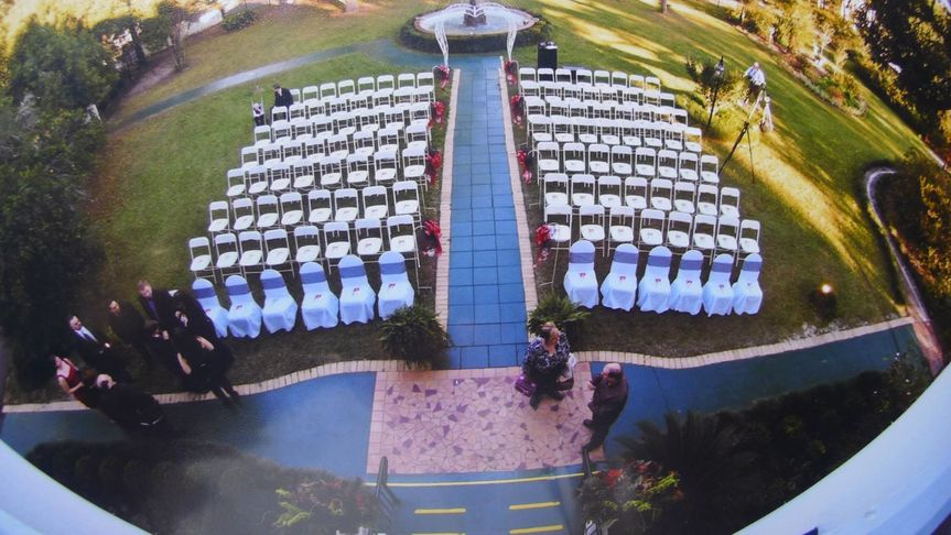 View of the front grounds wedding ceremony set up from the second floor balcony- chair covers and...