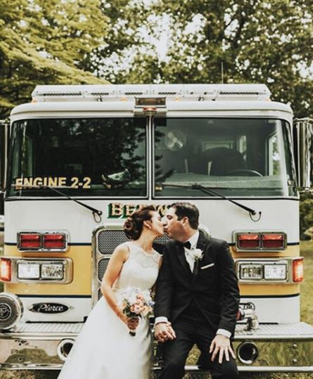 Newlyweds kissing by the truck