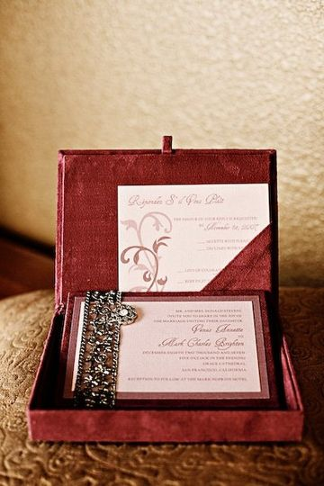 A microsuede box houses a coordinating invitation in varying shades of plum and purple. It is...