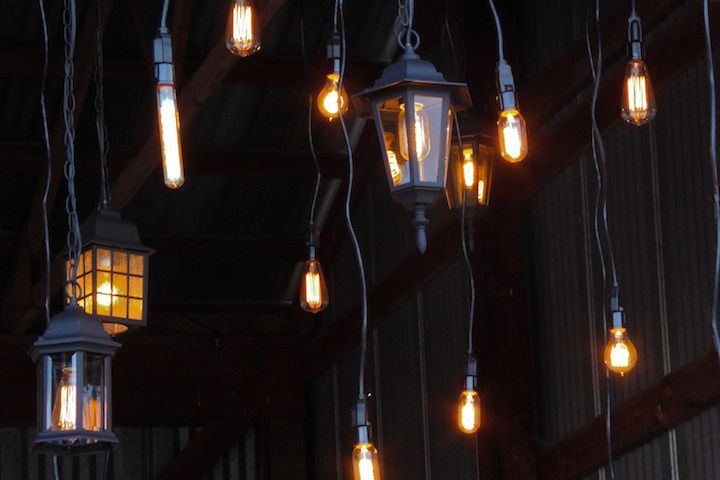 We hung fabulous clusters of hurricane lanterns and bare edison bulbs over lounge areas the...