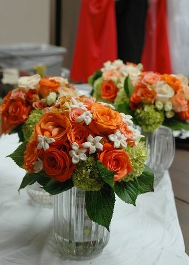 Fragrant stephanotis peeking out between bright orange roses and green hydrangeas.