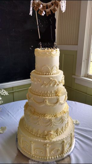 Old fashioned piping adorn this wedding cake.  Fun bottom tier, camo cake inside!