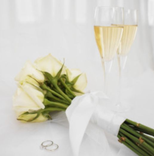 Couple's wedding ring with bouquet and glasses of wine