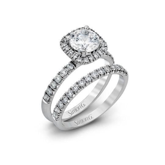 Style MR2132  This elegant classic white gold halo engagement ring and band is set with .78 ctw...