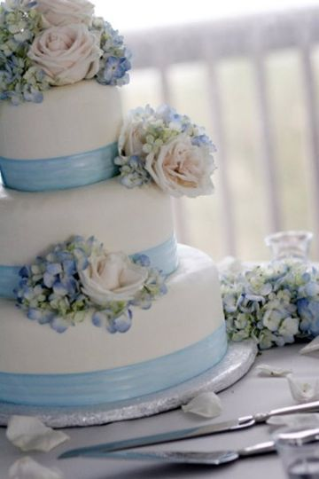 White cake with blue ribbons and flower decor