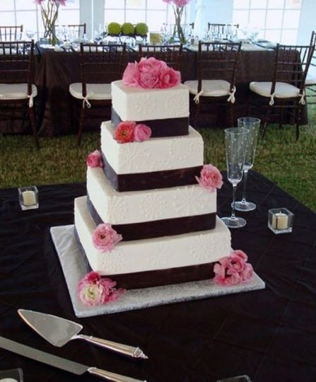 White cake with black ribbon bands and pink flowers
