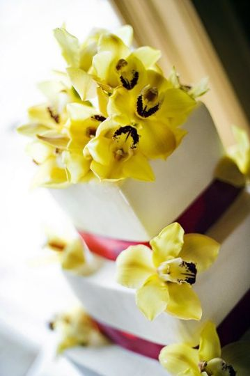 White cake with yellow flower decorations