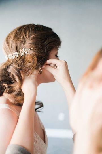 Putting on the bride's earrings