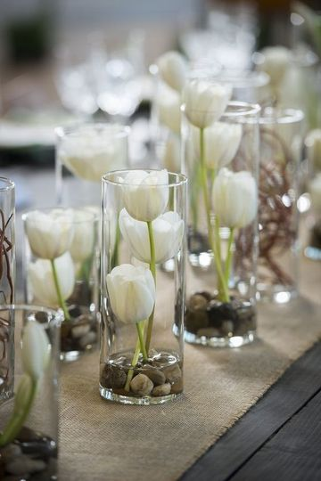 White tulips in column vases centerpieces