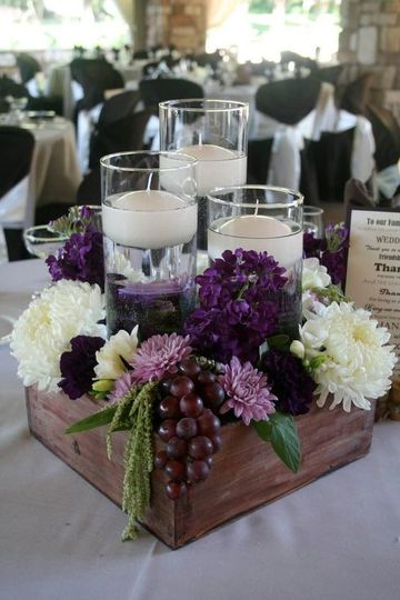 Wooden box with flowers, vases with candles, and berries centerpiece
