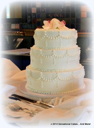 Classic white swags with fresh orchid topper in buttercream