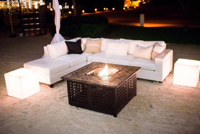 A sleek white sectional with a warm fire pit encourages conversation among your guests.