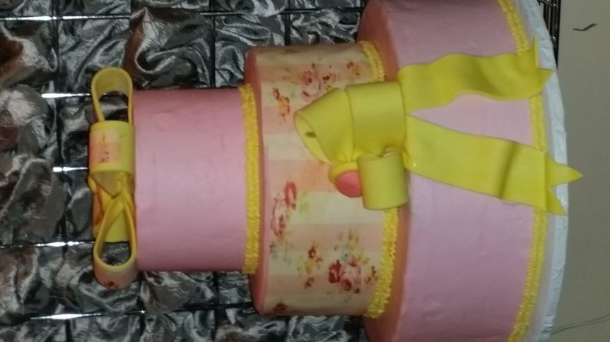 Soft pink buttercream with vintage print on middle tier, abstract fondant bow and ribbon