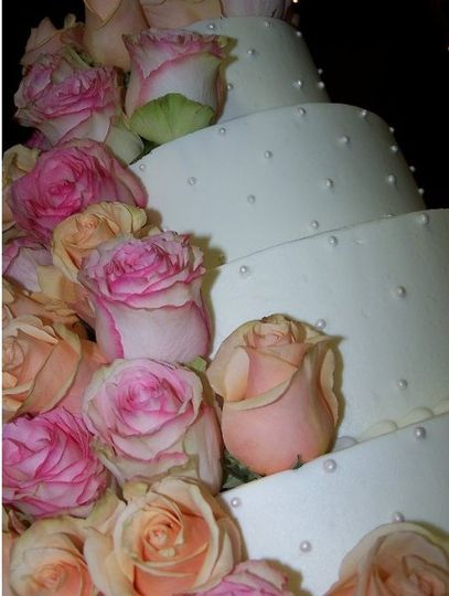 4-tier buttercream with edible pearls and fresh cabbage roses