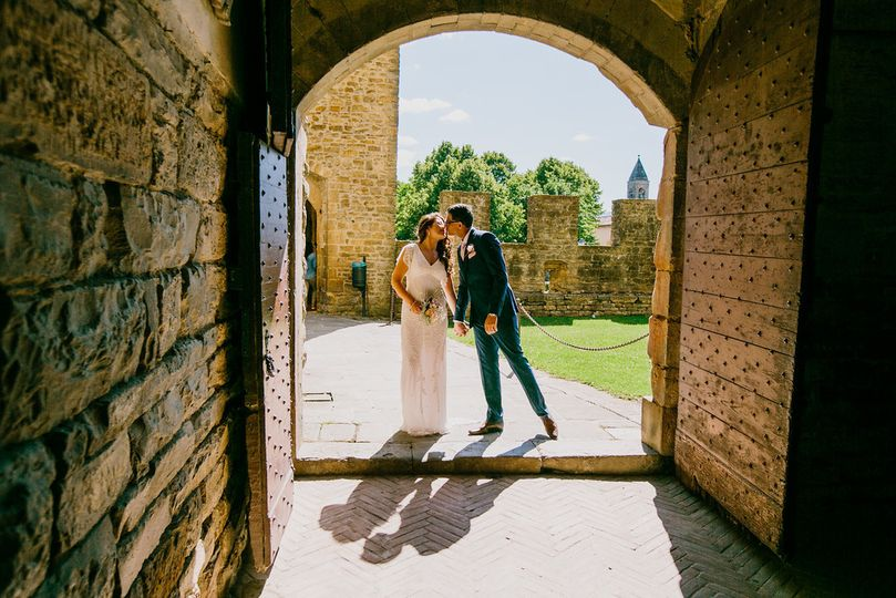 Romantic kiss at the entrance of medieval castle in Tuscany