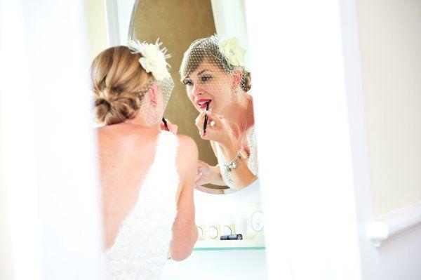 Bride applying lipstick