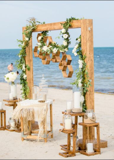 Modern beach wedding featuring our Valerie Structure and rustic pedestal trios