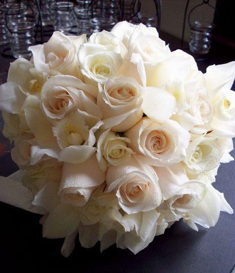 white,cream roses, white  cymbidium finished with cream satin.