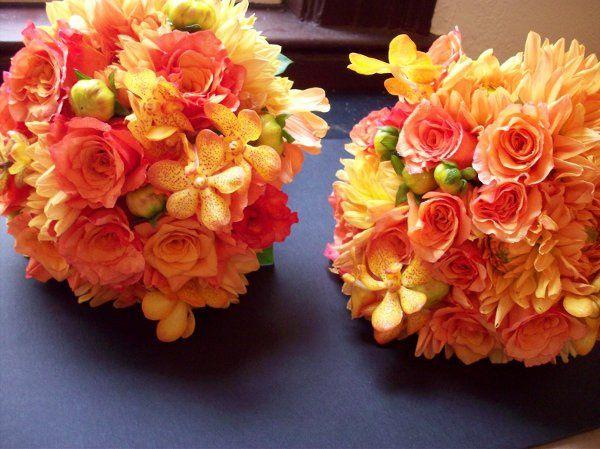 orange roses, orange vanda orchids, orange dahlias finished with burgundy satin.