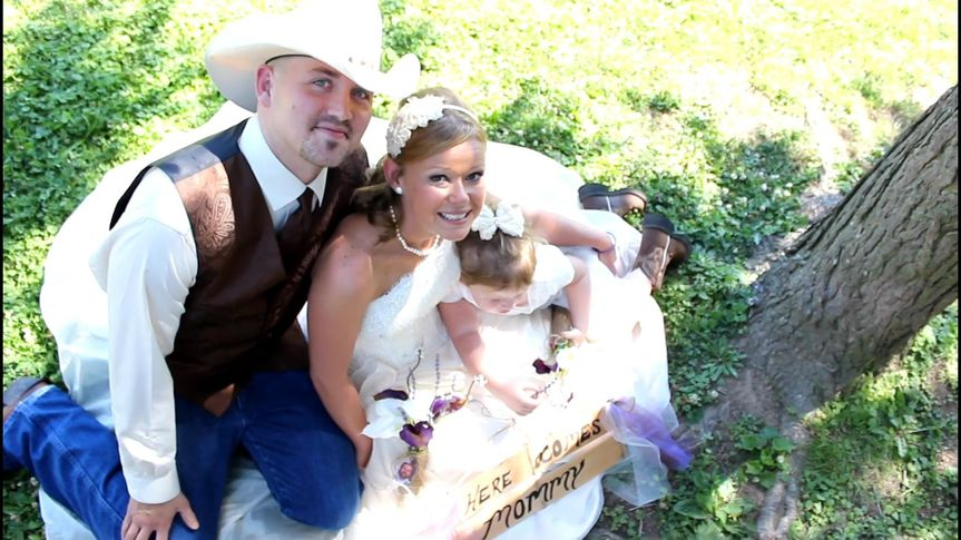 """Katti and Nathan pose with their little daughter holding her """"Here Comes Mommy"""" sign.  How adorable!"""