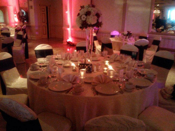 Gold Ballroom set up with Red Uplighting and Black Chair Sashes.
