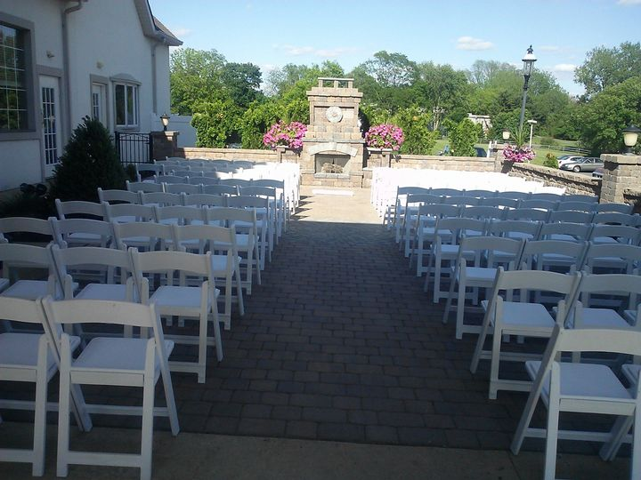 Ceremony Set up on the Gold Ballroom Patio with a lit fireplace and waterwalls on either side of the...