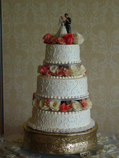 Three tier wedding cake with warm colored flowers