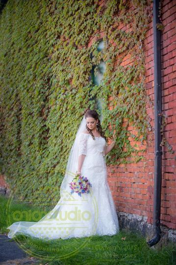 Bride by the brick wall