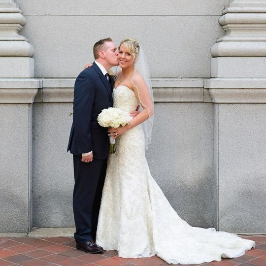 Groom kisses his bride's cheek